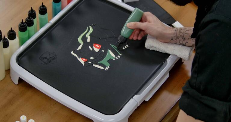 Bulbasaur pancake art step 4.1: Begin filling in the dark blue green shadows under bulbasaur's head and arms.