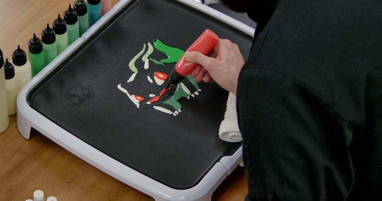 Bulbasaur pancake art step 5.1: Draw a red curved line for bulbasaur's tongue, and color in the mouth above with red batter.