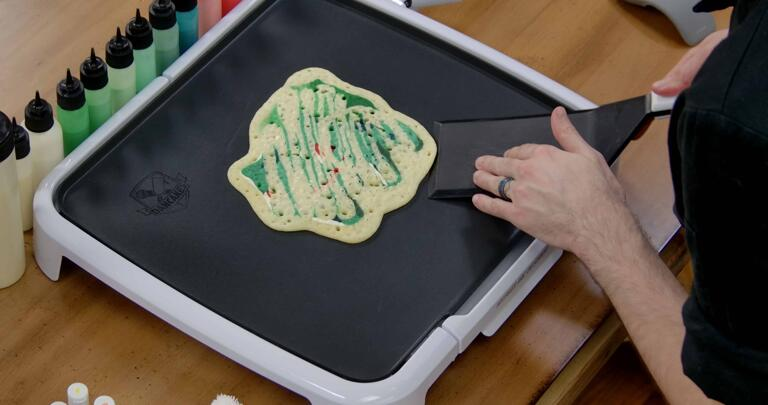 Bulbasaur pancake art step 8.2: When the pancake has cooked through, bubbles will appear and pop on the back, and the batter will no longer appear shiny. At this point, you can begin working your spatula under the pancake around the edges, to gently 'release' it from the griddle.