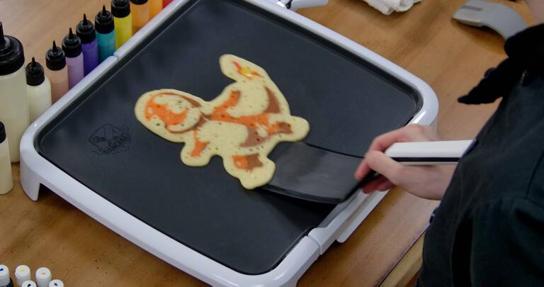 Charmander Pancake Art step 10.1: When your pancake is loose from the griddle, it's time to flip! With confidence, slide your spatula under the pancake...