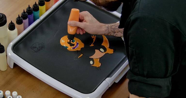 Charmander Pancake Art step 6.1: With your bold orange batter, begin filling in the rest of Charmander's face, arms, legs, and the top of Charmander's tail.