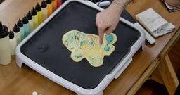 Squirtle Pancake Art step 7.2: As the pancake cooks you'll see bubbles appear on the back, like so. You want bubbles to appear across the whole back and for the batter to stop looking shiny as the pancake cooks through.