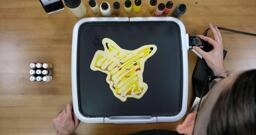 Pikachu Pancake Art step 8.1: Once your pancake design is filled, outlined, and there's nothing else to add, it's time to cook! I usually cook my pancakes around 225 degrees - hot enough to cook the batter, but not hot enough to brown it so much that you lose your color fidelity. Remember not to touch the surface of the griddle after this! You can burn yourself, so be careful.