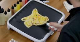 Pikachu Pancake Art step 9.1: When it's time to flip, the key is confidence! Be gentle and firm - align your spatula at the edge of your design, slide it under...
