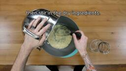 """This image shows the dry powder being stirred into the water in a mixing bowl with a whisk, and says """"then stir in the dry ingredients."""""""