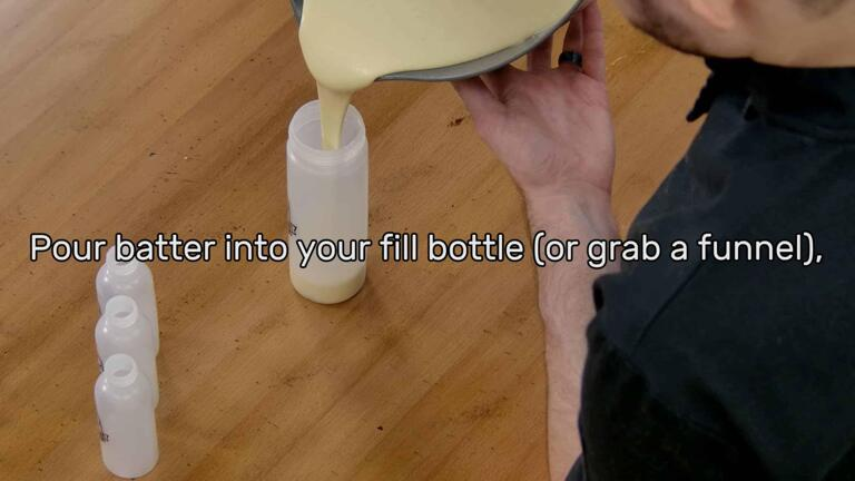"""This image shows the batter being poured into the Dancakes Fill Bottle from the mixing bowl, and says """"Pour batter into your fill bottle (or grab a funnel)"""""""