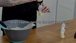 """This image shows pancake batter being poured from a fill bottle into a batter pen, and says """"...and fill batter pens to the halfway point."""""""