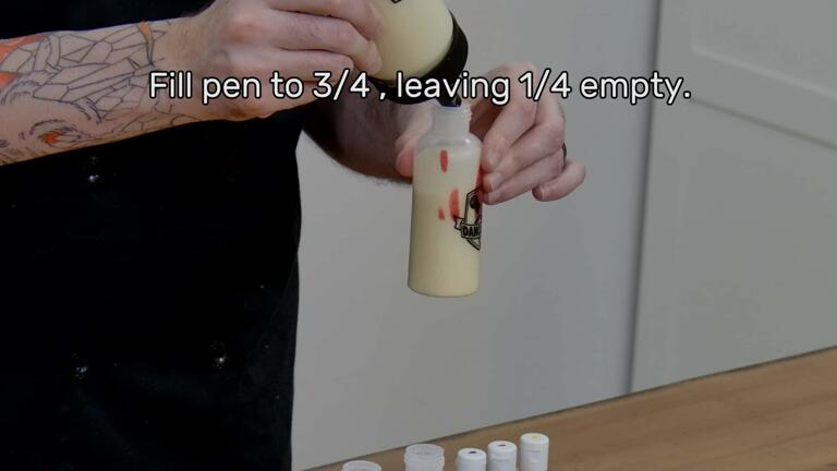 """An image of a batter pen, with red gel coloring added, being filled with a little more pancake batter. The image reads """"Fill pen to 3/4, leaving 1/4 empty."""""""