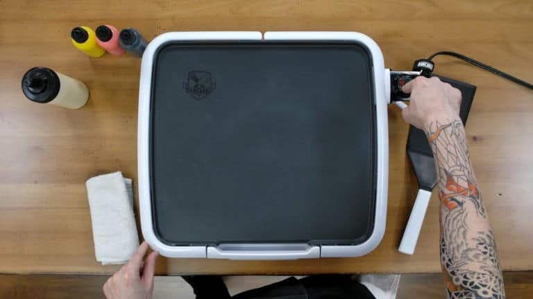 An image of the dancakes pancake art griddle, with the artist's hand pointing to the thermostate to indicate that the griddle is set to 'OFF'.