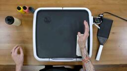 An image of the dancakes pancake art griddle, and the artist is resting their drawing hand on a folded-over white washcloth, demonstrating how artists can use folded hand towels to lend their drawing hand more stability without risking a burn.