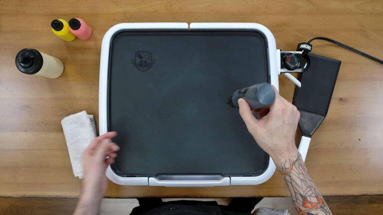An image of the dancakes pancake art griddle, over which the artist is gently gripping a black batter pen, demonstrating how suction can be used to prevent batter from pouring out automatically - a technique called 'squeeze control'.