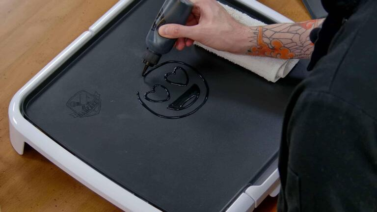 An image of a pancake art design being outlined in black batter on the dancakes griddle. The design is of a heart-eyes emoji, and it is incomplete.