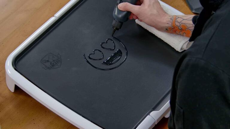 An image showing the black outlines of a heart eyes emoji being drawn onto the dancakes griddle with pancake batter.