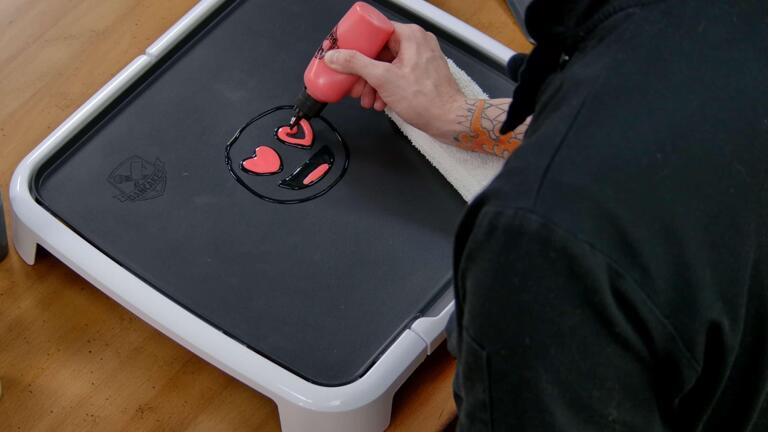 An image showing the black outlines of a heart eyes emoji pancake design being filled in with red batter, in the mouth adn heart-shaped eyes.