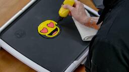 An image showing a heart eyes emoji pancake design having its yellow face colored in, the red eyes and mouth already having been colored in.