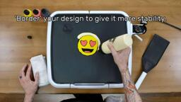"""An image of a completed heart-eyes emoji pancake design, face down on the griddle, while the artist uses their fill bottle to add a thick border of plain batter around the outside of this design. The image reads, """"'Border' your design to give it more stability."""""""