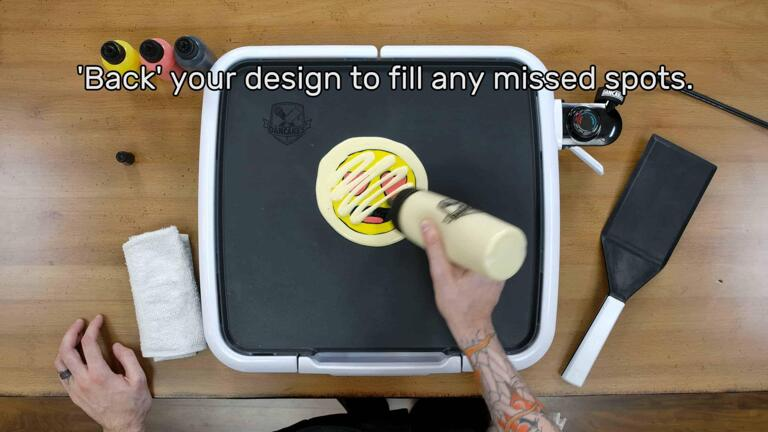 """An image showing the artist drizzling a zig-zag of plain batter across the back of the heart-eyes emoji design. The image reads """"'Back' your design to fill in any missed spots."""""""