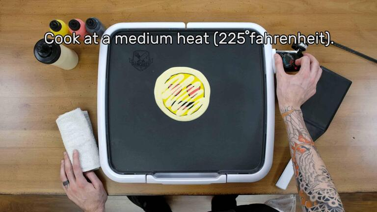 """An image that shows the artist adjusting the griddle thermostat to 225 degrees fahrenheit, which is labelled as 'Cook' on the dancakes griddle. The image reads """"Cook at a medium heat (225 degrees fahrenheit)."""""""