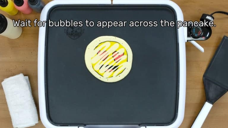 "An image of a heart-eyes emoji pancake design that has been bordered and backed, beginning to bubble on the griddle as it cooks. The image reads ""Wait for bubbles to appear across the pancake."""