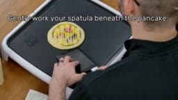 "This image shows the artist, holding the spatula, starting to slide the spatula under and around the pancake design, which is gently stuck in place. The image reads ""Gently work your spatula beneath the pancake."""