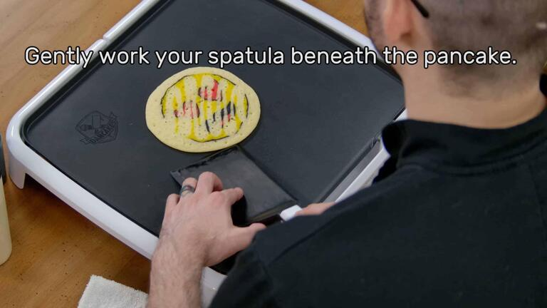"""This image shows the artist, holding the spatula, starting to slide the spatula under and around the pancake design, which is gently stuck in place. The image reads """"Gently work your spatula beneath the pancake."""""""