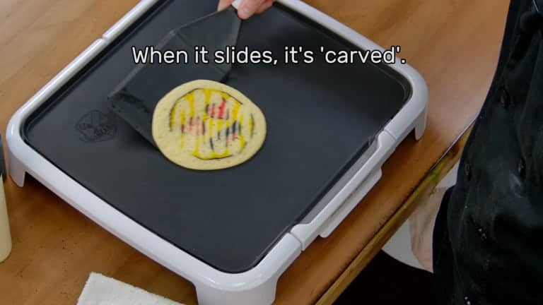 "This image shows the artist, holding the spatula, sliding the pancake design around (the design appears with a motion blur in the photo). The image reads ""When it slides, it's 'carved'."""