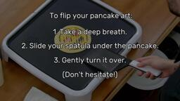 """An image of a spatula about to slide under the heart eyes emoji pancake art design. The image has been faded out to reveal a list of text that reads: """"To flip your pancake art: 1. Take a deep breath. 2. Slide your spatula under the pancake. 3. Gently turn it over. (Don't hesitate!)"""""""