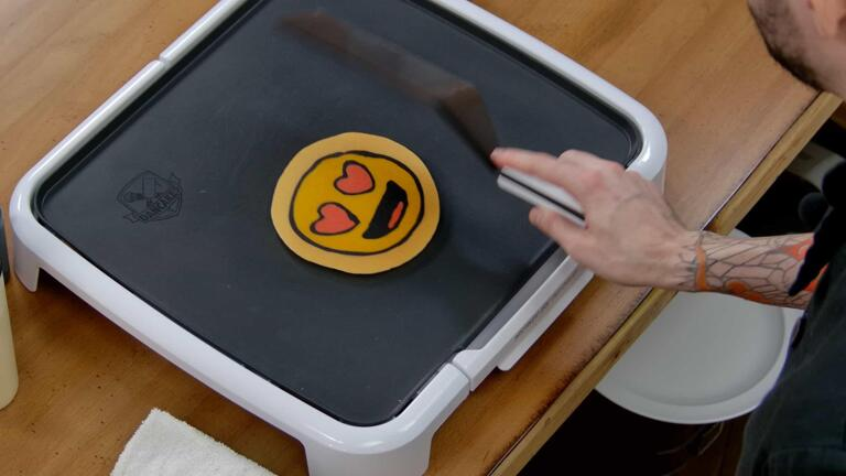 An image that shows the heart eyes emoji pancake design hit the griddle as it is flipped over, revealing its final appearance. The spatula is in frame, with a motion blur.