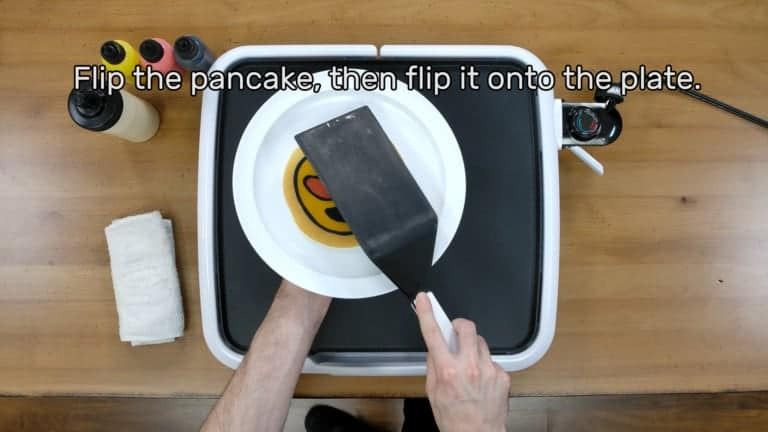 "An image of the heart eyes emoji pancake design being flipped onto the plate. The image reads: ""Flip the pancake, then flip it onto the plate."""
