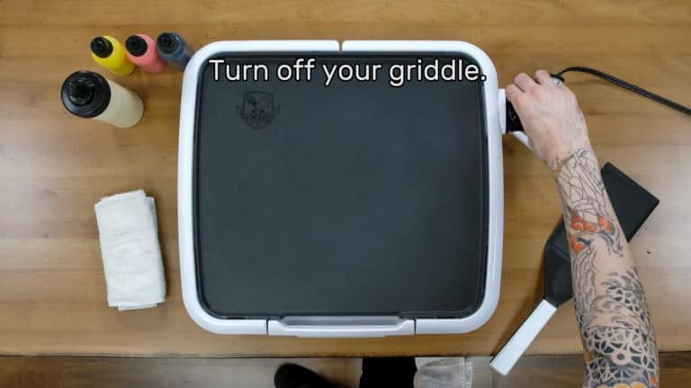 "An image of the artist reaching forward and turning the griddle thermostat to 'off'. Text on the image reads ""Turn off your griddle."""