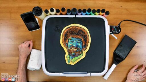 A pancake art portrait of Bob Ross with blue hues used for the face.