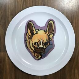 An image of a pancake drawn in the shape of a cute french bulldog, hiding its nose behind a blanket.