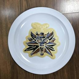 An image of a pancake drawn in the shape of Geralt's Medallion from The Witcher novel and video game series.