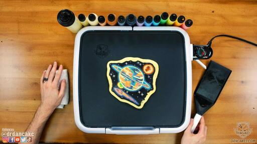 A photo of the pancake art design crafted in episode 3 of the joy of pancakes, showing a scene of planets with a space ship floating in space.