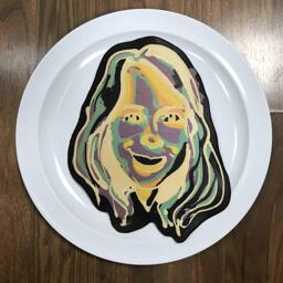 An image of a pancake drawn in the shape of a woman using negative colors, to create a strange psychedelic effect.