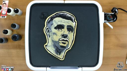 An image of a pancake art portrait of social media personality Gary Vaynerchuck, rendered in grayscale and pictured resting on the dancakes griddle from a top-down viewing angle. The warm brown wood of the countertop and the multicolored batter pens adorn the edges of this simple image.