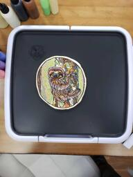 Pancake art of a pensive, contented sloth clinging to a lichen-covered tree and gazing at the viewer with a knowing smile. The sloth emits undulating rays of green and white light, beckoning the viewer to relax and be at peace. The illustration is colored with many contrasting lines and hatchings, and filled with a psychedelic rainbow palette that makes it all feel dreamlike.