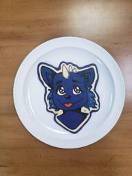 Pancake art of a midnight blue anthro/furry character with their tongue sticking out, blue sideburns, and big, shiny purple eyes and white horns on the top of their head. A stark outline of white batter makes the design pop.