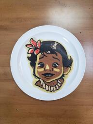 Pancake art of baby Moana from the animated film, Moana. She looks curious and excited, and has a bright pink flower in her hair.