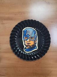 Pancake art of Captain America, wearing his blue hood/cap with a large white 'A' emblazoned across. He has a disgruntled facial expression.
