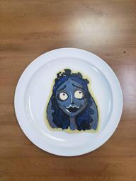 Pancake art of Emily from Corpse Bride, looking disarmingly above and to the right. Her hair is dark blue and her fae and veil are a cool grey.