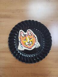 Pancake art of a simple cartoon cat with orange fur, a white snout, and yellow highlights. The cat is smiling with its tongue out and its eyes closed, and looks content.