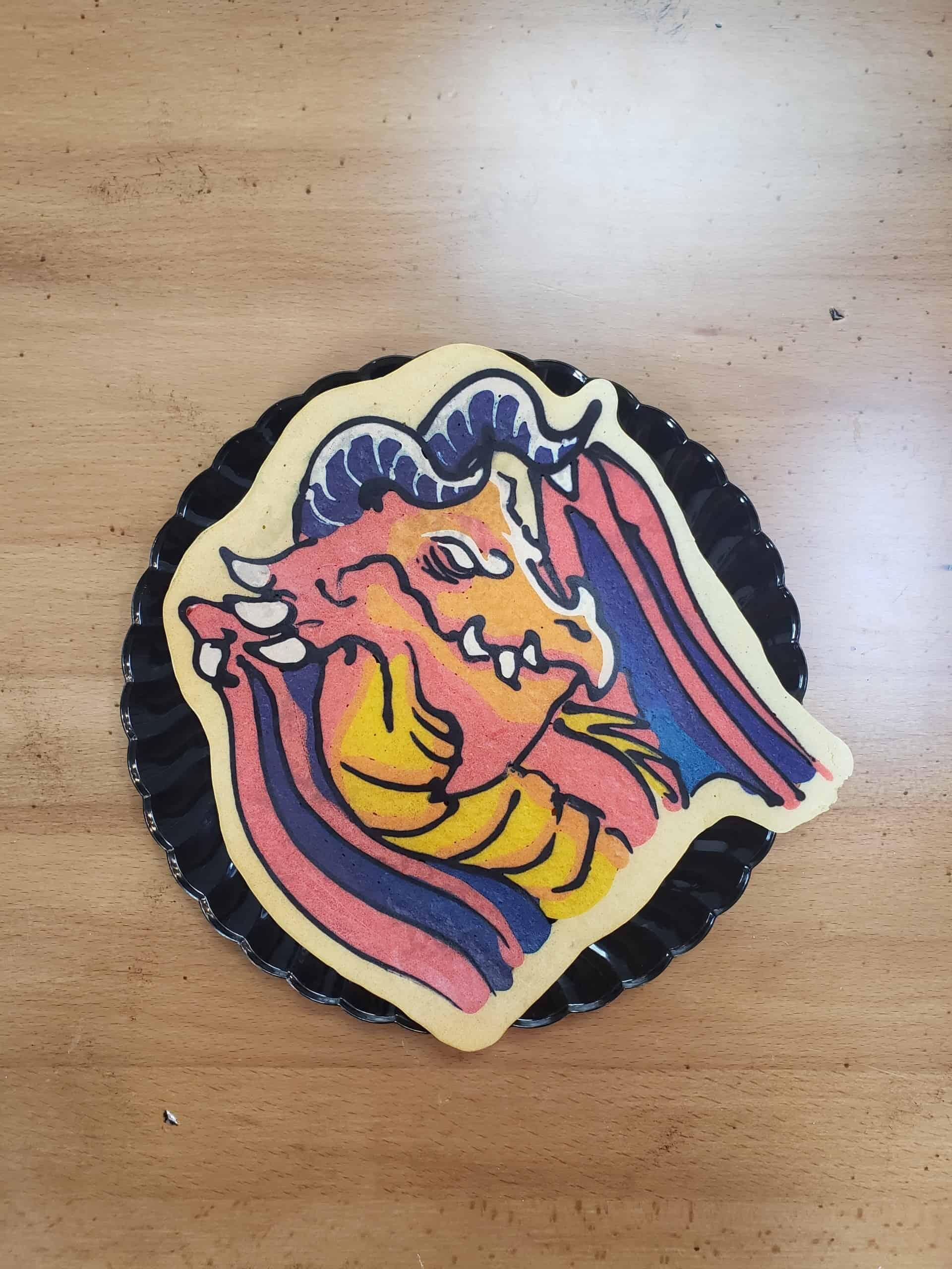Pancake art of a red dragon with a vicious scowl and white eyes with no pupils. Its chest scales are golden yellow and the skin of its wings are a deep purple, and it has two curved horns atop its head.