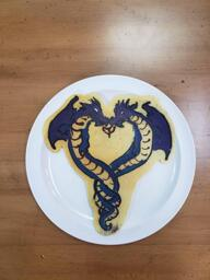 Pancake art of two purple serpent dragons with single winges entwined in the shape of a heart. A small spit of flame comes from each of their mouths to create the point in the center of the heart.