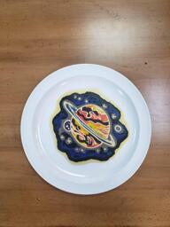 Pancake art of a simple abstact space scene, in which a large planet with an atmosphere of roiling reds, oranges, browns and yellows (with simple rings around it like Saturn) sits against a black backdrop with a few stars, two smaller moons, and a blue/purple mixture of nebulous space gasses giving is some mysterious character.