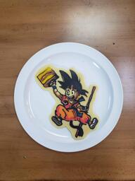 Pancake art of a young Son Goku (from the dragonball anime) holding his staff and carrying a suitcase, smiling as though he is about to go on vacation. He has his monkey tail extended beneath him.
