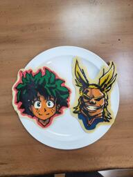 Pancake art of Midoriya and All Might from the popular anime My Hero Academia. Midoriya has an unkempt tousle of dark green hair and a bright, open expression of contenment, and All Might has a dramatic hairstyle with two arcing yellow locks almost like rabbits ears or antennae, and his prideful, mighty facial expression with his wide, full-teethed smile, is cast in heavy shadow, as though he is looking down on the viewer from a high, well-lit place.