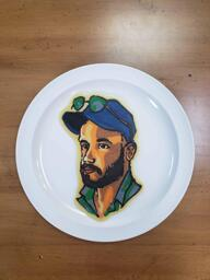 Pancake art of a white man with dark brown beard, an open-collared turquoise button-up shirt, and a blue baseball cap atop which sits a pair of green sunglasses. He is gazing off into the distance at a 3/4 turn from the viewer.