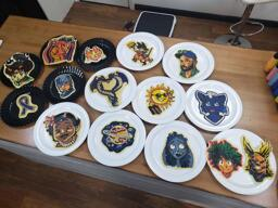 A collected shot of all of the different pieces of pancake art that were made during the September 13 2020 request livestream. All of the pancakes in this gallery are present, placed across the rich wood color of the dancakes studio countertop. You can see the displaced griddle resting on the floor just in the background, and a few of the color bottles used to make these pancakes rest off to the right side of the photo.