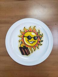 Pancake art of a yellow sun with sunglasses, casually saluting and carrying a brown suitcase as if it is about to go on vacation. It has a cheeky smile.
